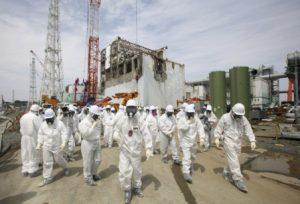 Para pekerja di Tokyo Electric Power Co (TEPCO), mengenakan pakaian pelindung dan masker, sedang berjalan di depan Reaktor Nulir Nomor 4 di Fukushima Daiichi. Reaktor ini mengalami kebocoran akibat tsunami. (Photo : Reuters)