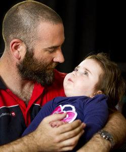 Bayi perempuan bernama Violet Stephen sedang digendong ayahnya, David. Violet merupakan salah satu bayi yang mengidap penyakit TAY-SACHS. (Credit: MAARTEN HOLL/Fairfax NZ)
